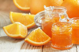 Orange jam and fresh oranges